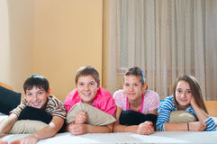 Quatre amis d'adolescent heureux se trouvant sur le bâti Image stock