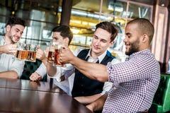 Quatre amis d'hommes d'affaires boivent de la bière et passent le temps ensemble dans a Photographie stock