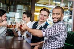 Quatre amis d'hommes d'affaires boivent de la bière et passent le temps ensemble dans a Photographie stock libre de droits