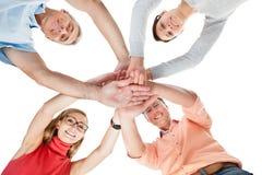 Quatre amis d'une cinquantaine d'années occasionnels tenant des mains Image libre de droits
