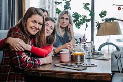 Quatre amis dans le café regardent l'appareil-photo et rient Photo stock