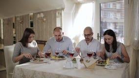 Quatre amis dans le restaurant, mangent de la viande et boire du vin rouge dans le verre clips vidéos