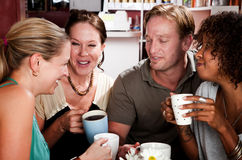 Quatre amis dans un café Photo stock