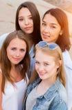 Quatre amis de femle regardant amicaux l'appareil-photo, sourire, heureux les gens, mode de vie, concept d'amitié photo stock