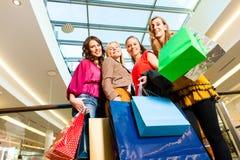 Quatre amis de femmes faisant des emplettes dans un mail Photographie stock libre de droits