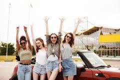 Quatre amis de jeunes femmes tenant la voiture proche dehors Images libres de droits