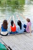 Quatre amis de l'adolescence heureux s'asseyant sur le pilier de la rivière ou du lac Photos libres de droits