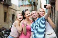 Quatre amis de sourire gais prenant l'autoportrait Photos libres de droits