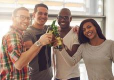 Quatre amis de sourire tapant des bouteilles à bière Photo stock