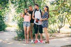 Quatre amis drôles prenant le selfie avec un téléphone intelligent en parc Photos libres de droits