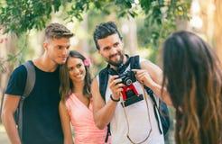 Quatre amis drôles prenant le selfie avec un téléphone intelligent en parc Image stock