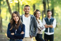Quatre amis en parc, foyer sur la femme avec des bras croisés Photos libres de droits