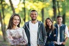 Quatre amis en parc, foyer sur la femme avec des bras croisés Image stock