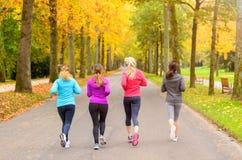 Quatre amis féminins courant ensemble en automne Photographie stock