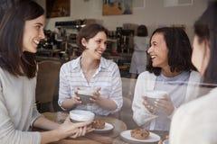 Quatre amis féminins détendant au-dessus du café à un café photographie stock