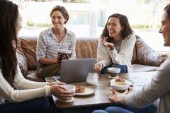 Quatre amis féminins parlant au-dessus du café à un café image libre de droits