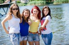 Quatre amis féminins s'approchent de la berge Image libre de droits