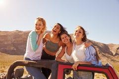 Quatre amis féminins sur le voyage par la route se tenant dans la voiture convertible Images stock