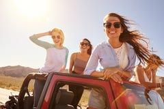 Quatre amis féminins sur le voyage par la route se tenant dans la voiture convertible Photos stock