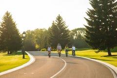 Quatre amis faisant un cycle en bas de la route Image stock