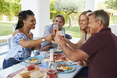 Quatre amis faisant un pain grillé à une table de dîner sur un patio Photos libres de droits