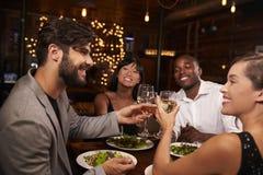 Quatre amis faisant un pain grillé au-dessus de dîner à un restaurant Photographie stock libre de droits