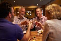 Quatre amis faisant un pain grillé pendant un repas à un restaurant Image stock