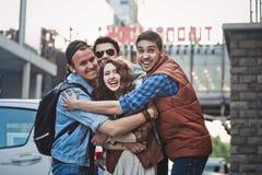 Quatre amis gais étreignant sur la rue Images libres de droits