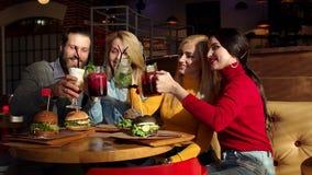Quatre amis gais font tinter les cocktails et la limonade régénérateurs lumineux dans le café clips vidéos