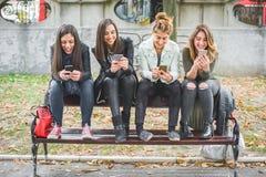 Quatre amis heureux à l'aide des téléphones portables sur le banc de parc Photographie stock libre de droits