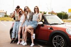 Quatre amis heureux de jeunes femmes tenant la voiture proche dehors Image stock