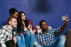 Quatre amis heureux font le selfie de groupe avec le mobile Photo stock