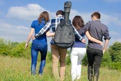 Quatre amis heureux marchant ensemble dehors Photographie stock libre de droits