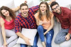 Quatre amis heureux riant tout en se reposant sur le divan Image stock