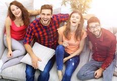 Quatre amis heureux riant tout en se reposant sur le divan Photo libre de droits