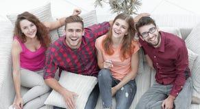 Quatre amis heureux riant tout en se reposant sur le divan Image libre de droits