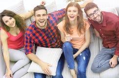 Quatre amis heureux riant tout en se reposant sur le divan Images libres de droits