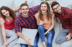 Quatre amis heureux riant tout en se reposant sur le divan Photos libres de droits