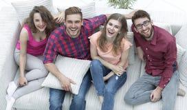 Quatre amis heureux riant tout en se reposant sur le divan Photographie stock