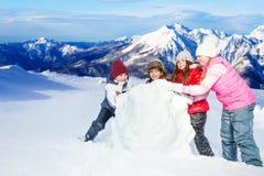 Quatre amis heureux roulant la boule de neige à l'hiver Photo stock