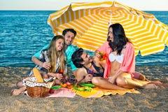 Quatre amis insouciants assis sous le parapluie jaune Image libre de droits