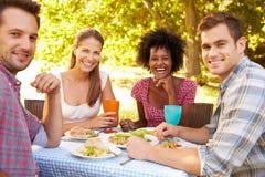 Quatre amis mangeant ensemble dehors Images stock