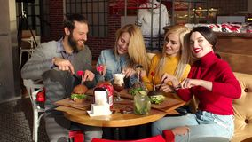 Quatre amis mangent des hamburgers et boivent de la limonade dans un caf? ensoleill? lumineux banque de vidéos