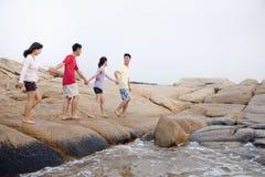 Quatre amis marchant au-dessus des roches par la mer Photographie stock libre de droits