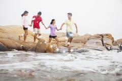 Quatre amis marchant au-dessus des roches par la mer tenant des mains Photographie stock
