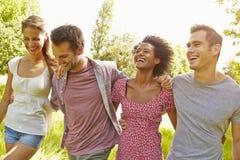 Quatre amis marchant ensemble dans la campagne Photos libres de droits