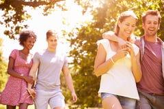 Quatre amis marchant ensemble dans la campagne Photos stock