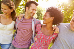 Quatre amis marchant ensemble dans la campagne Photo stock