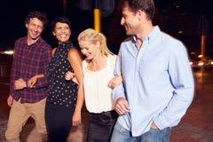 Quatre amis marchant par la ville ensemble la nuit Photographie stock libre de droits