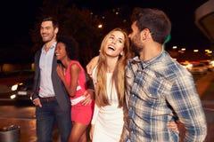 Quatre amis marchant par la ville ensemble la nuit Photo libre de droits